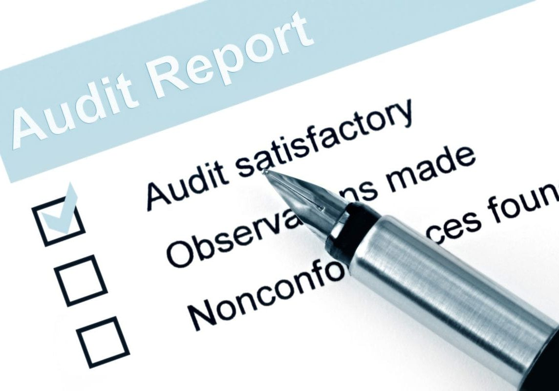 """Fountain pen over audit report, with checkmark against """"audit satisfactory""""."""